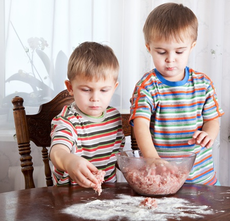 only 1 boy: Cute boys are mixing mincemeat in a bowl Stock Photo