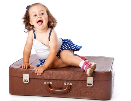 only girls: A little girl on the suitcase. Isolated on a white background