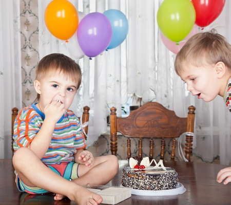 Birthday party. Two boys are flowing on the cake photo