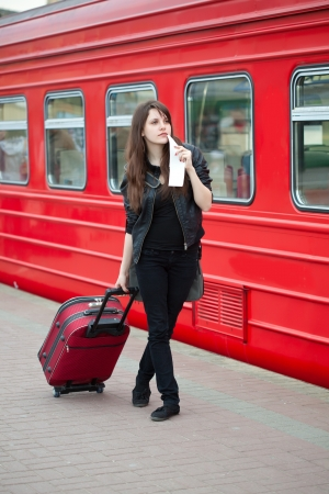 Young woman with suitcase is waiting a train photo