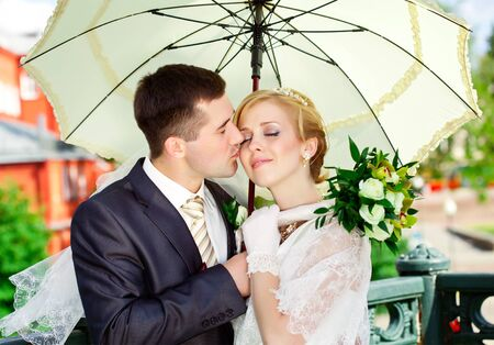 Young blonde bride and groom in walking the park photo