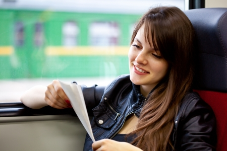 train ticket: A beautiful woman in the train with ticket in her hands Stock Photo
