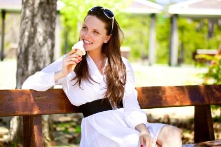 sadece kadınlar: Bir gülümseyen bir kadın parkta bir dondurma yiyor