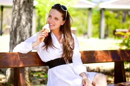 A smiling woman is eating an ice cream in the park