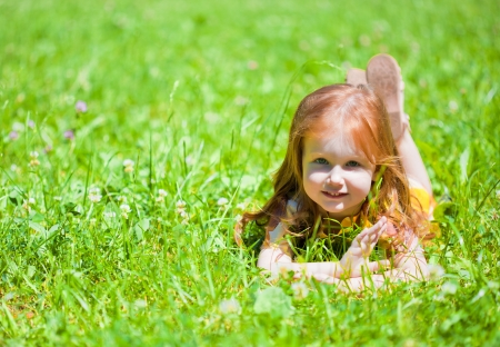 A smiling small girl is lying on the meadow