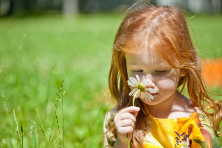 A smiling ginger-haired girl with a flower in the field photo