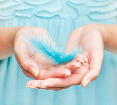 Womans hands with feather close-up Stock Photo