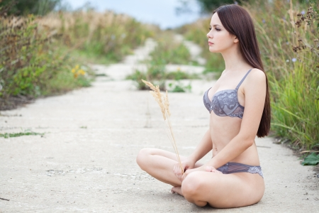 naked woman sitting: A beautiful woman in underwear is sitting on the dirt road
