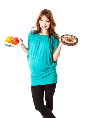 ginger haired: A pregnant smiling young woman is holding food in her hands  Isolated on a white background