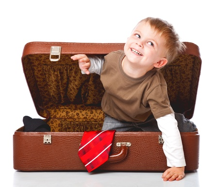 packing suitcase: A funny boy with sombrero is sitting in the suitcase. Isolated on a white background