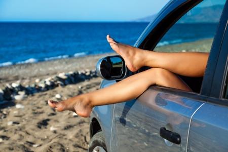 piernas mujer: Piernas de la mujer est�n colgando hacia fuera una ventana de coche Foto de archivo