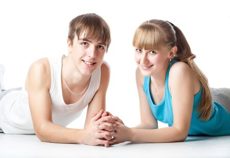 young couple smiling: Sports couple is lying in the studio. Isolated on a white background Stock Photo