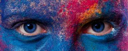 Eyes of woman with unusual paint make-up on black background photo
