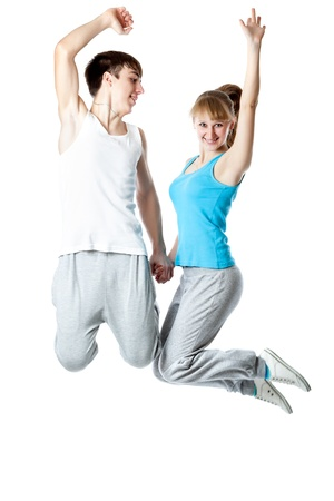 affectionate actions: The young couple is jumping in a studio. Isolated on a white background