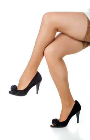 Beautiful slim legs in stockings and black shoes photo