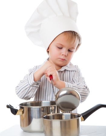 a funny cute boy is portraying a cook. isolated on a white background photo