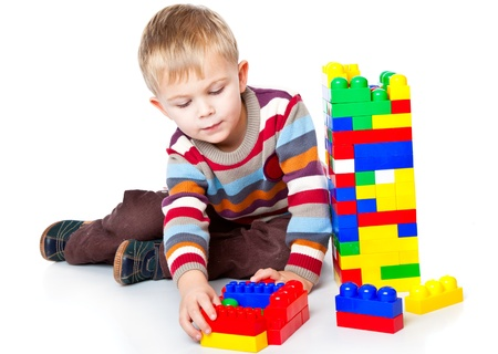 a funny boy is playing with lego. isolated on a white background Standard-Bild
