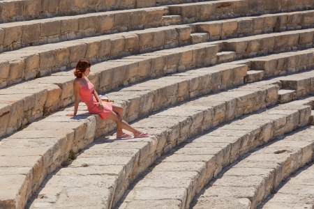 Beautiful girl is sitting on the steps of amphitheater photo
