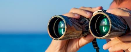loin: un homme se tourne vers les jumelles sur mer Banque d'images