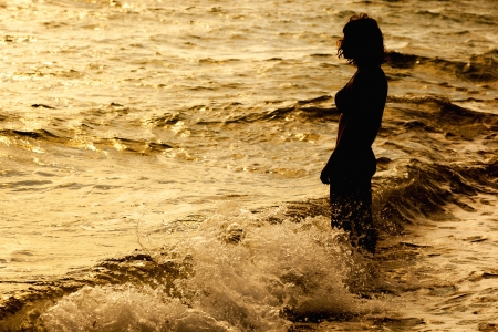 Woman is standing near the sea. Sunset photo