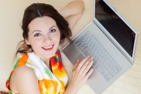 A smiling woman with laptop is on the sofa photo