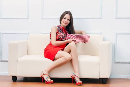 A beautiful woman with gift is sitting on the sofa photo