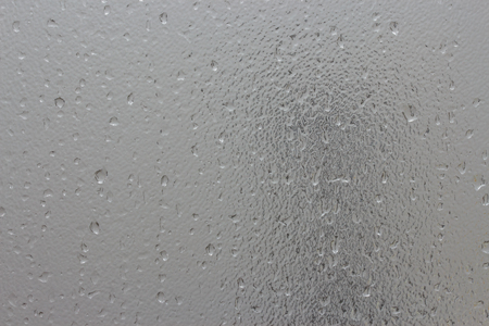 Water drops on frosted glass with faded shadow