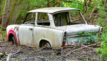 An abandoned Trabant is stuck in the mud.