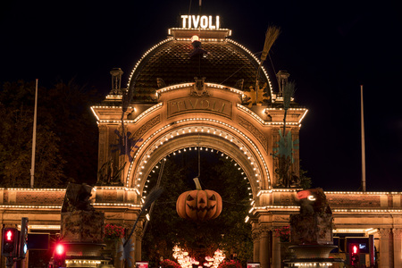 Halloween pumpkin in front of the illuminated main entrance to Tivoli Gardens. Tivoli Gardens one of Denmarks most famous tourist attractions and the oldest amusement park in the world.