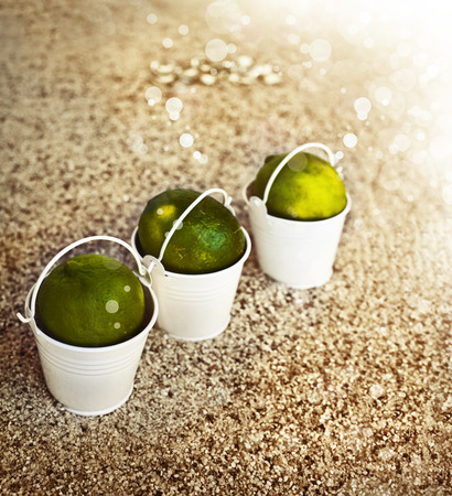 Little white buckets with limes on the sandy beach. Summer holiday concept background, travel themes with cocktail umbrella photo