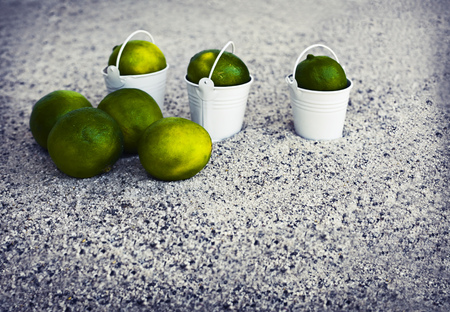cocktail umbrella: Little white buckets with limes on the sandy beach. Summer holiday concept background, travel themes with cocktail umbrella