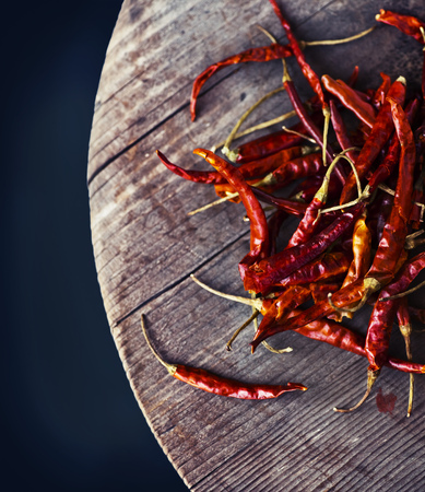 food photography: Red hot chili peppers on an old wooden table texture. Spicy pepper. Food photography with cope space. Shallow depth of field, selective focus Stock Photo