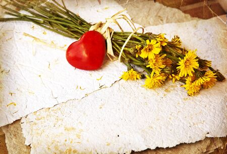 bouquet of dandelions on handmade paper with little red heart. Love letter. Summer background. Vintage card photo