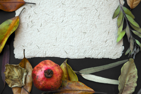 pomegranat: Fall background with Old hand made paper with pomegranat fruit, yellow autumn leaves over dark surface