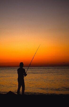 Shore Fisherman in Sunset photo