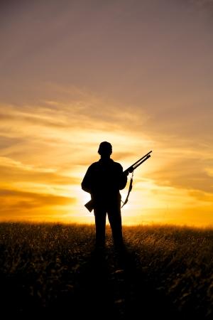 mujer con arma: Mujer Hunter en Sunrise