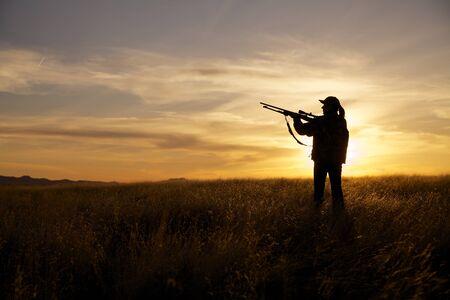 夕暮れ時の女性のライフル ハンター 写真素材
