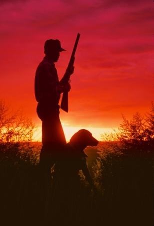 Bird Hunter and Dog in Sunrise Foto de archivo