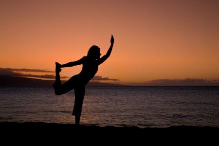 Woman Practicing Yoga on Beach at Sunset photo