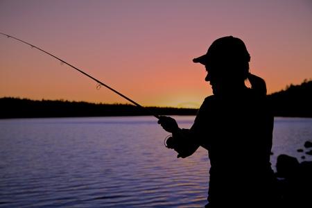 Donna di pesca nel tramonto Archivio Fotografico - 19122065