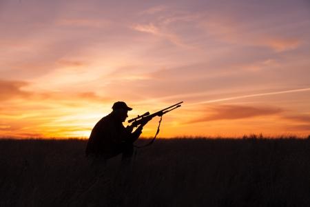 夕日にシルエットのライフルを持つハンター 写真素材