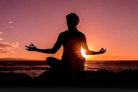 Vrouw beoefenen van yoga bij zonsondergang op een strand van Maui Stockfoto