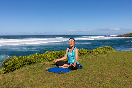 Woman Practicing Yoga on the Maui Coast Imagens - 100160918