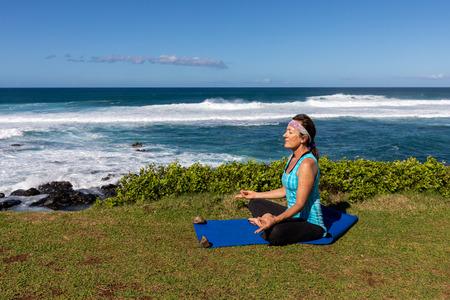 Woman Practicing Yoga on the Maui Coast Imagens - 100155638