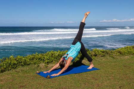 Woman Practicing Yoga on the Maui Coast Imagens - 100160919