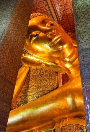 Reclining Buddha gold statue face  Wat Pho, Bangkok, Thailand photo