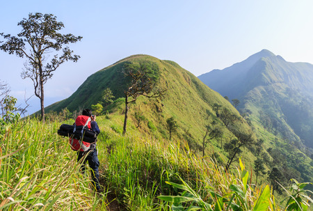 Backpacker going to the top of mountain