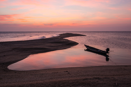 long tailed boat: Sunset with long tailed boat cast anchor.