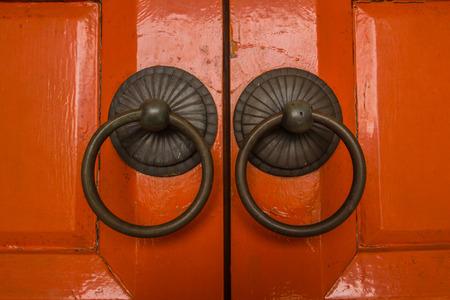 The door knocker found on orange old door. photo
