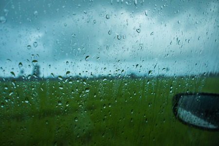 drizzle: Rain drops on the glass windows car. Stock Photo